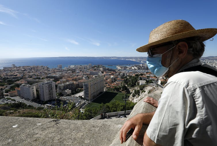 A man wearing a protective face mask looks out on Marseille.