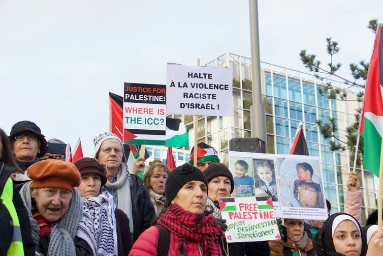 Protesters in front of the ICC building hold sigs saying 'Where is the ICC?' and 'Justice for Palestine'