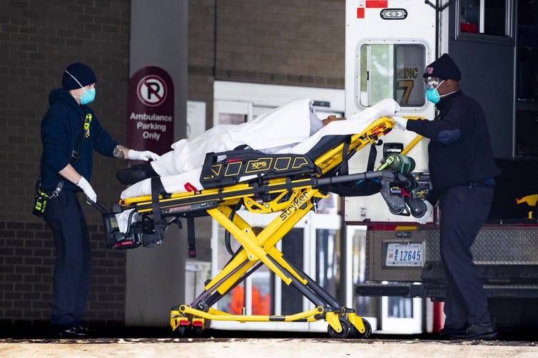 A patient being transferred from an ambulance into hospital on a trolley