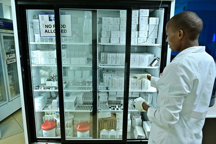 A man in a lab coat stands in front of a freezer filled with medical supplies.