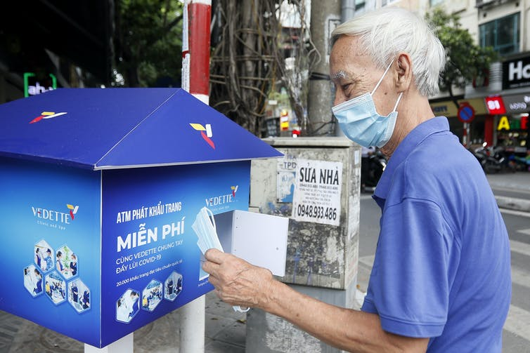 A man taking a disposable mask from a box in Hanoi, Vietnam