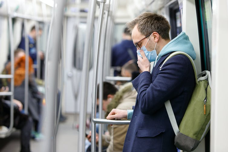 A man in a face mask coughing on public transport.