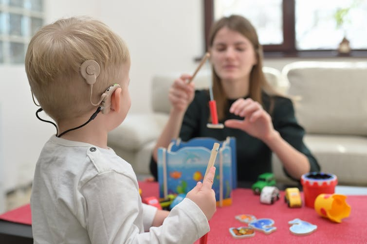 A young child wears a cochlear implact while playing with toys, sitting across from an adult.