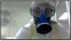 A researcher wears googles, a respirator and protective clothing inside a laboratory.
