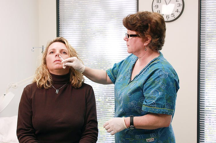 A woman receiving a nasal flu vaccine.
