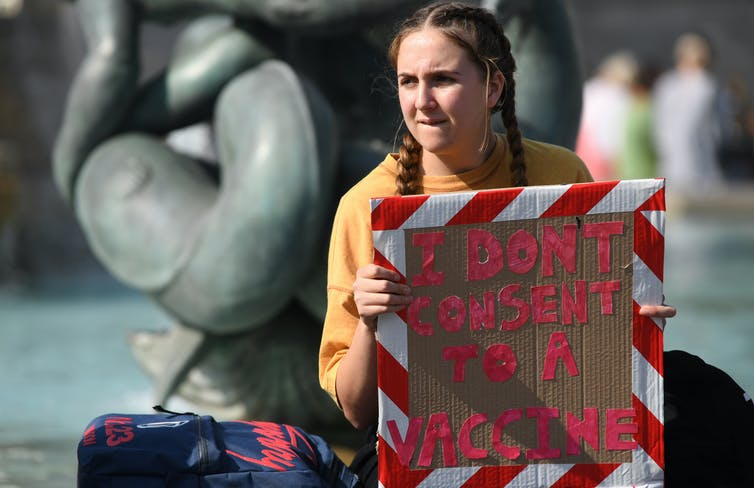 A girl holding a sign saying: 'I don't consent to a vaccine'