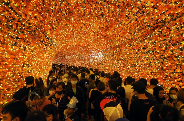 A large crowd of people walks through an orange tunnel.