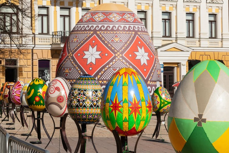 Artists display painted multicolored Easter eggs against the background of a historic building