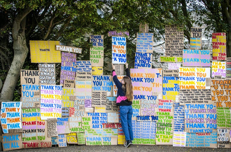 A girl in front of a wall of signs saying