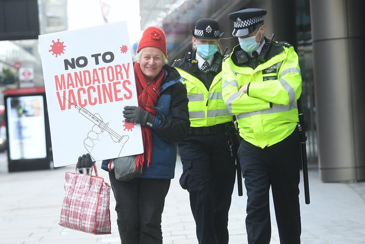 A protester in London holds a sign saying: No to mandatory vaccines.