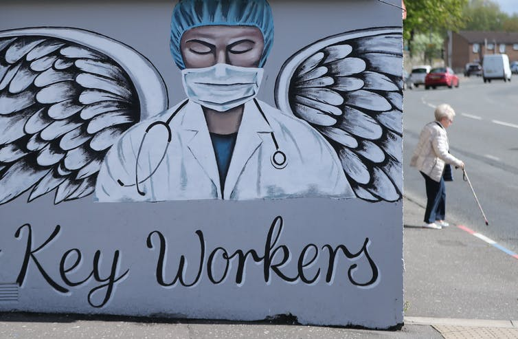 A mural of a doctor wearing PPE with angel wings above the words Key Workers'.