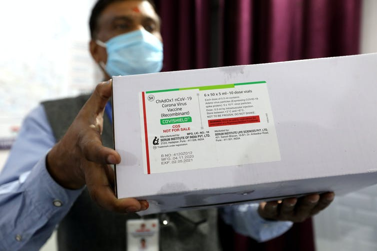 A man in India holds a box of Oxford vaccine doses, produced by the Serum Institute of India