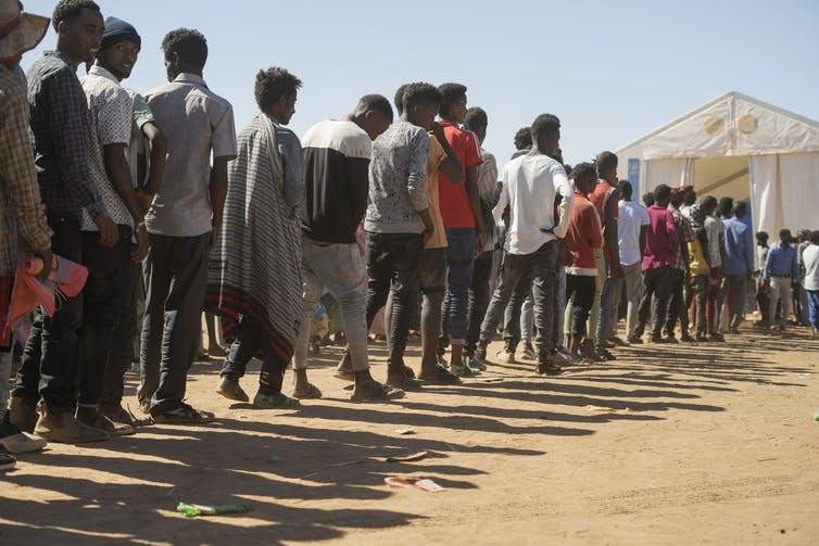 Ethiopian refugees from the Tigray region wait in line to receive aid at a refugee camp