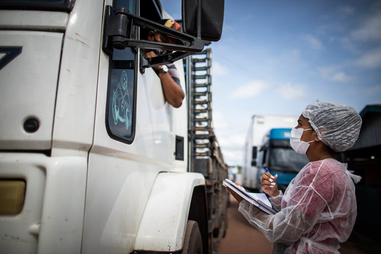 A woman in full PPE interviews a man in the cab of a lorry.