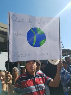 A man holds a sign in Spanish with a drawing of Earth.