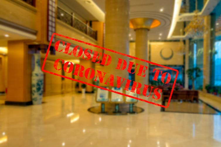Empty hotel lobby with a 'closed for coronavirus' sign