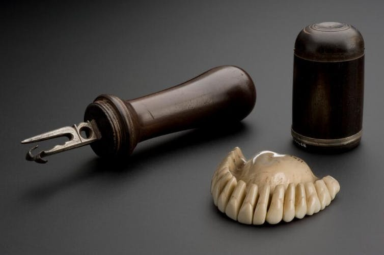 Set of ivory teeth and wooden tools on grey background.