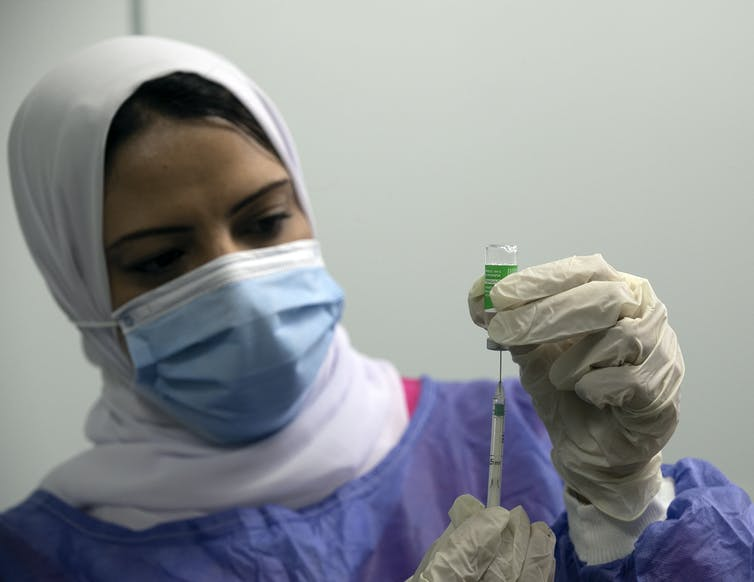 A health worker in Egypt loading a syringe with the Oxford/AstraZeneca vaccine
