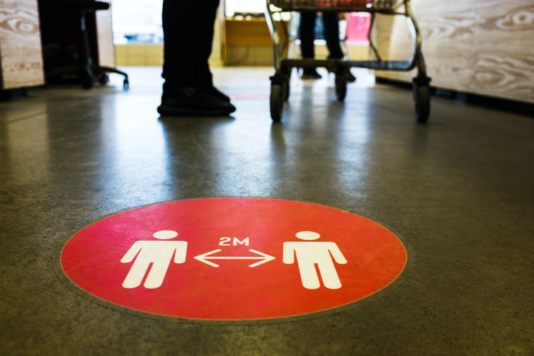 A sign on a supermarket floor promoting social distancing