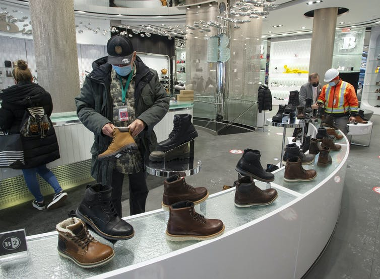 Customers in masks look at shoes in a shoe store.