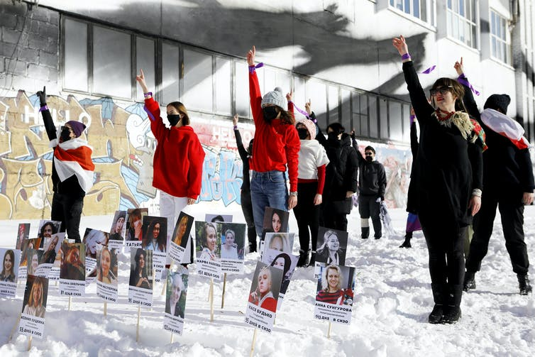 Women in red stand in the snow, holding fists in the air, with pictures of other women