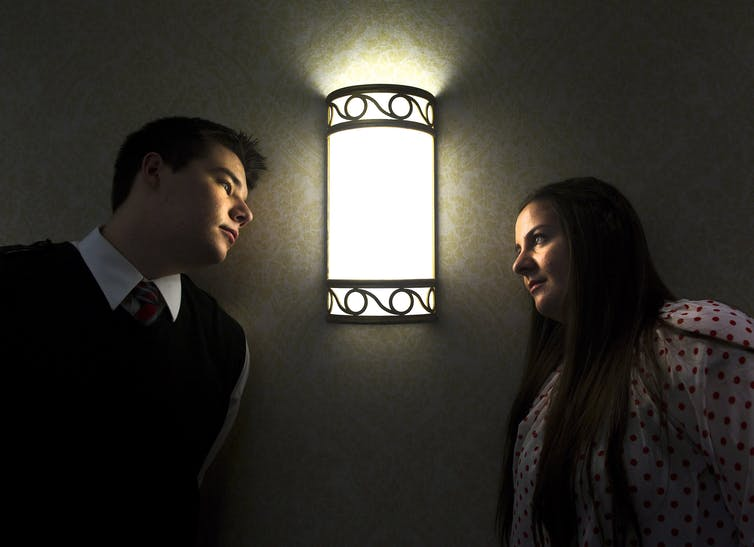 Teenage boy and teenage girl look at each in front of a light